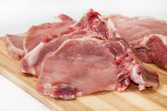 Fresh cut pork chops on wooden board Royalty Free Stock Photos