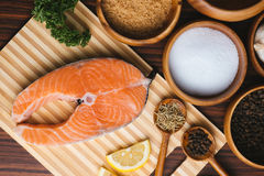 Fresh cut raw salmon on wooden board. Fresh cut salmon fillet on wooden chopping board with it& x27;s ingredients Royalty Free Stock Photos