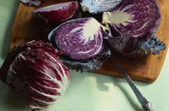 Fresh cut red cabbage on cutting board, red onion, red radicchio Royalty Free Stock Images