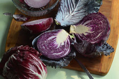 Fresh cut red cabbage on cutting board, red onion, red radicchio Royalty Free Stock Photo