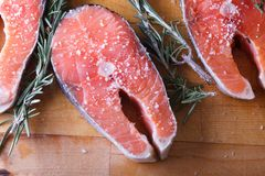 Fresh cut Salmon steaks. With salt and rosemary on wooden cutting board Stock Images