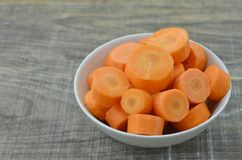 Fresh cut thick carrots on bowl on wooden. Fresh cut thick carrots on bowl Royalty Free Stock Photo