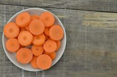 Fresh cut thick carrots on white bowl. Fresh cut thick carrots in bowl on wooden Royalty Free Stock Photo