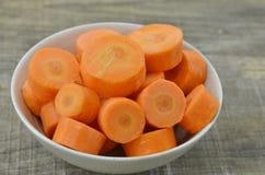 Fresh cut thick carrots on white bowl. Fresh cut thick carrots in bowl on wooden Royalty Free Stock Image