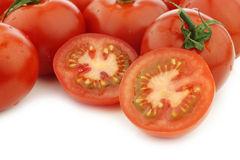 Fresh cut tomato and some whole ones. On a white background Stock Image