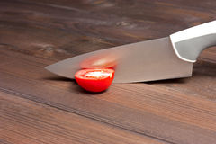 Fresh cut tomatoes with knife on the dark wooden table Royalty Free Stock Image