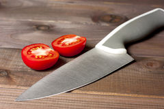 Fresh cut tomatoes with knife on the dark wooden table Stock Images