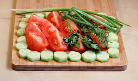 Fresh cut vegetables and greens. On the chopping board Stock Images