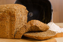 Fresh cutted loaf of rye bread and some flour on. Fresh cutted loaf of rye bread with breadmaker and gluten free flour on wooden table royalty free stock images