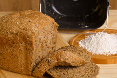 Fresh cutted loaf of rye bread and some flour on. Fresh cutted loaf of rye bread with breadmaker and gluten free flour on wooden table stock photo