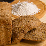 Fresh cutted loaf of rye bread and some flour on. Fresh cutted loaf of rye bread with breadmaker and gluten free flour on wooden table stock photos