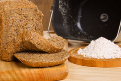 Fresh cutted loaf of rye bread and some flour on. Fresh cutted loaf of rye bread with breadmaker and gluten free flour on wooden table Stock Photography