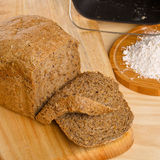 Fresh cutted loaf of rye bread and some flour on. Fresh cutted loaf of rye bread with breadmaker and gluten free flour on wooden table Royalty Free Stock Photography
