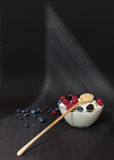 Fresh dairy product cottage cheese with berries in glass bowl with wooden spoon on black table Stock Photos