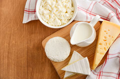 Fresh dairy products. Milk, cheese, brie, camembert and cottage cheese on the wooden background. Stock Photos