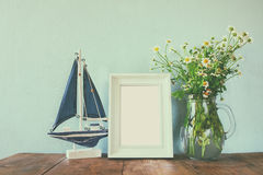Fresh daisy flowers, blank photo frame and wooden boat on wooden table. vintage filtered Royalty Free Stock Image