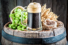 Fresh dark beer with big foam, hops and wheat. On old wooden barrel stock photography