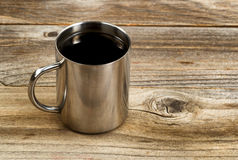 Fresh dark coffee in stainless steel cup on rustic wood Royalty Free Stock Images