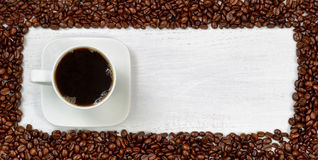 Fresh Dark Coffee surrounded by roasted coffee beans Stock Images