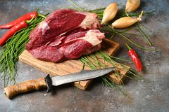 Fresh dark meat with ingredients for cooking on brown wooden cutting board. royalty free stock image