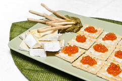Fresh delicatessen plate. Delicatessen plate with pesto sauce, Camembert cheese and red salmon roe Stock Photos