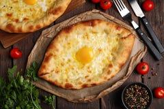 Fresh delicious Adjarian khachapuris served on wooden table, flat lay. Fresh delicious Adjarian khachapuris served on wooden table