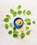 Fresh delicious baby spinach around bowl with lemon and spices on white wooden background, top view. Stock Images