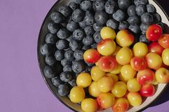 Fresh delicious bluberries and cherries in bowl on purple background. Superfoods. Vegan Royalty Free Stock Photography