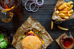 Fresh delicious burgers with french fries, sauce and beer on the wooden table top view Royalty Free Stock Photos