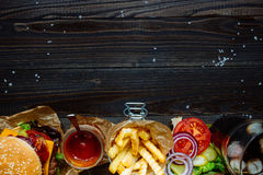 Fresh delicious burgers with french fries, sauce and drink on the wooden table top view, with copy space.  Royalty Free Stock Images