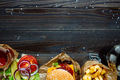 Fresh delicious burgers with french fries, sauce and drink on the wooden table top view, with copy space.  Royalty Free Stock Image