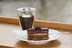 Fresh delicious cake with a glass of coffee beans Royalty Free Stock Image
