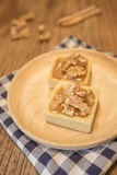 Fresh delicious caramel nut tart dessert on wooden plate Royalty Free Stock Photos