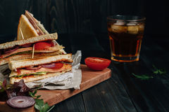 Fresh delicious club sandwich and drink on the wooden dark table Royalty Free Stock Photo