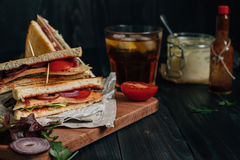 Fresh delicious club sandwich, sauces and drink on the wooden dark table Royalty Free Stock Images