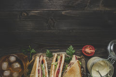 Fresh delicious club sandwich, sauces and drink on the wooden dark table Royalty Free Stock Photo