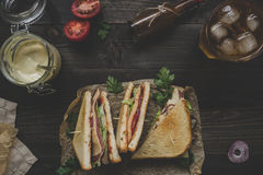 Fresh delicious club sandwich, sauces and drink on the wooden dark table Stock Images
