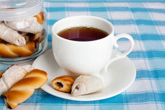 Fresh delicious cookies and hot tea on tablecloth Royalty Free Stock Photography