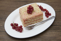 Fresh delicious diet cake with berry red currant at Dukan Diet on a porcelain plate with a spoon on a wooden background. Stock Image