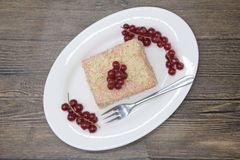 Fresh delicious diet cake with berry red currant at Dukan Diet on a porcelain plate with a spoon on a wooden background. Royalty Free Stock Images