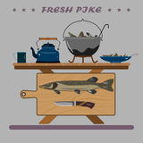 Fresh and delicious fish for your holiday. A big pike and a knife on the board. From below a folding table and a chair Stock Images