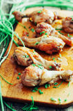 Fresh delicious fried chicken legs on a wooden chopping board decorated with fresh chives. Baked ham. Roasted chicken legs. Grille Royalty Free Stock Photo
