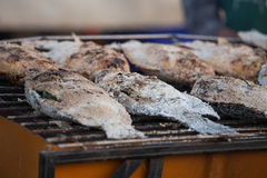 Fresh delicious grilled fish, tilapia, nile fish with salt. At market Stock Image