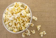 A bunch of freshly popped popcorn. Fresh, delicious hand-popping popcorn in a bowl on a rustic jute base Stock Photos