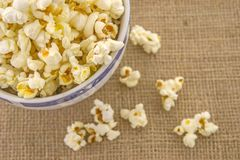A bunch of freshly popped popcorn. Fresh, delicious hand-popping popcorn in a bowl on a rustic jute base Royalty Free Stock Images