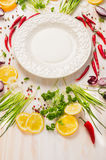 Fresh delicious herbs,spices and seasoning and empty plate on white wooden background Stock Images