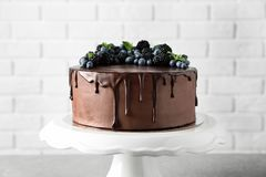 Fresh delicious homemade chocolate cake with berries on table. Against brick wall stock image