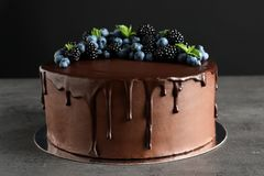 Fresh delicious homemade chocolate cake with berries. On table against dark background royalty free stock image