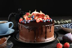 Fresh delicious homemade chocolate cake with berries on table against dark background royalty free stock photos