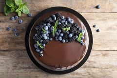 Fresh delicious homemade chocolate cake with berrie. S on wooden table, top view stock photo